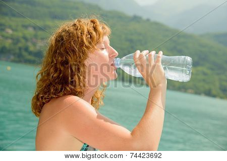 Young Woman Drinks Water With A Bottle