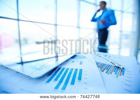 Papers, digital tablet and pen on background of businessman by office window
