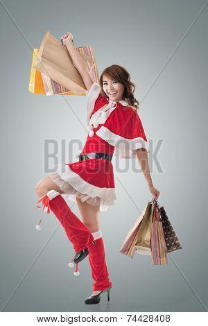 Asian Christmas girl hold shopping bags, full length portrait.
