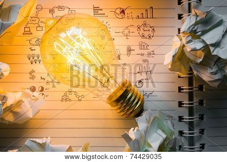 Note book and light bulb with drawing graph on wood table