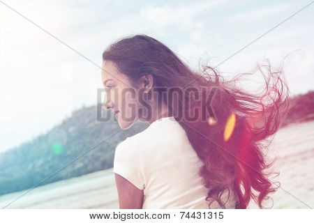 Pretty Young Long Hair Woman with Wavy Hair Blown by Wind, Looking to Her Left. Captured at Rear View.