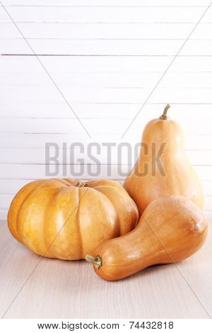 Three pumpkins on wooden table on wooden wall background