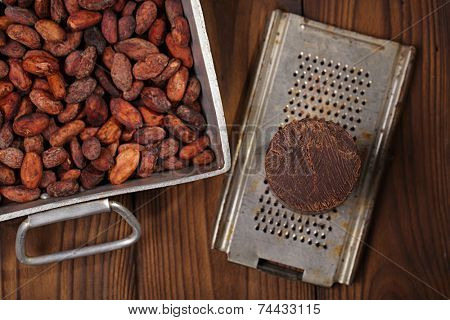 roasted cocoa beans in Vintage heavy cast aluminum roasting pan and and 100% solid chocolate on wood background