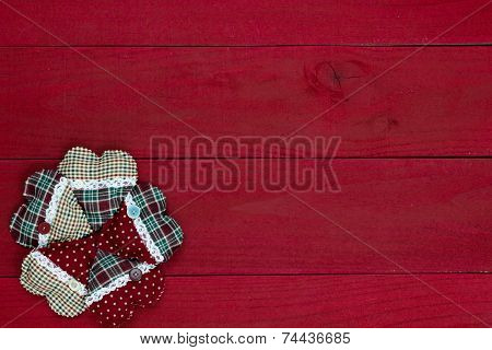 Cluster of plaid country Christmas hearts border dark red wooden background