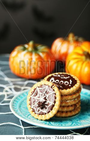 Tasty Halloween cookies on plate, on decorative spiderweb