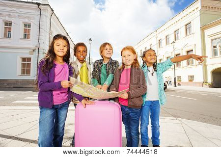 International kids standing with map and  luggage