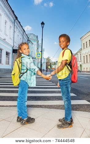 Two African kids hold hands, stand near crossroad