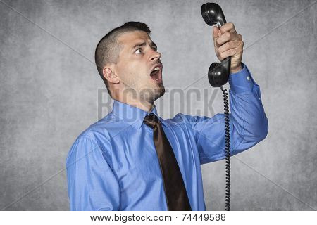 Angry Businessman Screaming During A Telephone Conversation