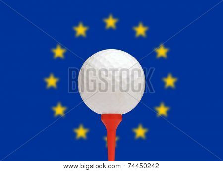 Golf ball on tee in front of the flag of the European flag