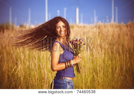 smiling beautiful woman with long curly hair in motion  hold in hand a bouquet of wild flowers in  grass field