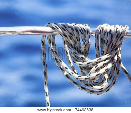 Ropes or mainsheets on the deck of sailboat hanging on a background of blue sea water.