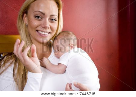 Young mother holding newborn baby boy in arms