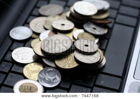 A Shot Of A Laptop And World Coins In An Office Environment, Can Be Used As E-commerce Concept