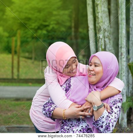 Happy Southeast Asian Muslim mother and daughter at outdoor park, family lifestyle.