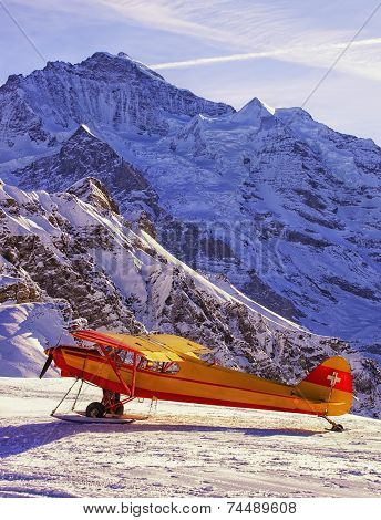 Yellow Red Airplane At The Mountain Airfield In Front Of Peaks In Swiss Alps
