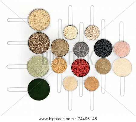 Body building powders and health food in metal scoops over white background.