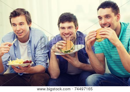 friendship, food and leisure concept - smiling friends with soda and hamburgers at home