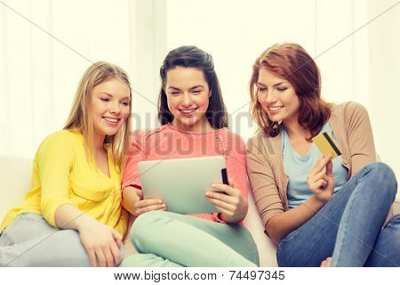 friendship, money, technology and internet concept - three smiling teenage girls with tablet pc computer and credit card at home