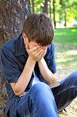 foto of sorrow  - Sorrowful Teenager sitting in the Park near the Tree - JPG