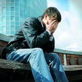 picture of sorrow  - Toned photo of Sorrowful Teenager sitting on the City Street - JPG
