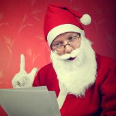 Picture of santa claus reads a letter.