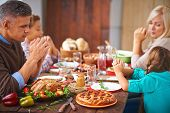 picture of praying  - Portrait of modern family of four sitting at festive table and praying - JPG