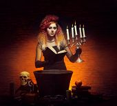 picture of dungeon  - Young and beautiful witch making a witchcraft in dungeon - JPG
