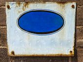 image of crude  - Textured blue rusty metal background with crude painted oval shape - JPG