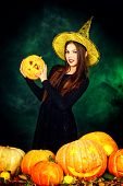stock photo of teen smoking  - Pretty teen girl in a costume of witch standing with pumpkins over dark smoky background - JPG