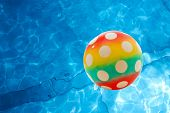 stock photo of beach-ball  - Ball over the rippling surface of a pool - JPG