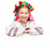 stock photo of national costume  - smiling little girl in the Ukrainian national costume behind white board with space for text - JPG