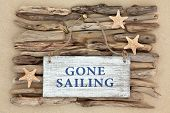 foto of driftwood  - Starfish and gone sailing old weathered sign on driftwood and beach sand background - JPG