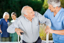 stock photo of nursing  - Male and female nurses helping senior people in nursing home - JPG