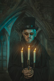 foto of wraith  - Strange and scary man standing with a candelabrum in which candles are burning - JPG