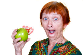 stock photo of false teeth  - Elderly lady losing her teeth on a bite of an apple - JPG