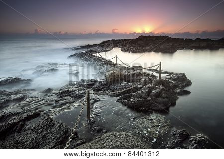A steel rope wards off the ocean at an ocean bath