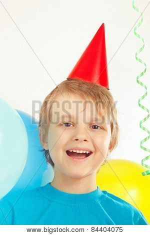 Little blonde boy in holiday cap with festive balls and streamer