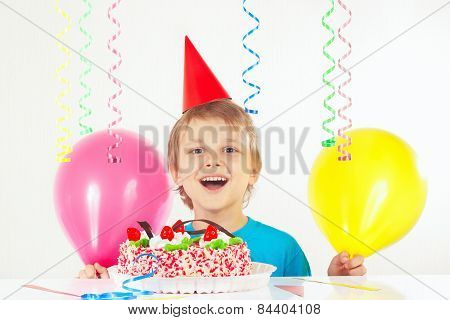 Little blonde boy in holiday cap with birthday cake and balloons