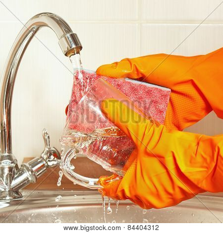 Hands in gloves wash the glass over the sink in kitchen