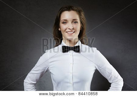 Smiling young waitress in bow-tie