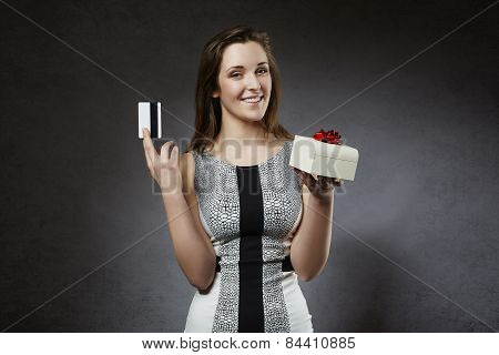 Young cheerful woman holding credit card and gift box