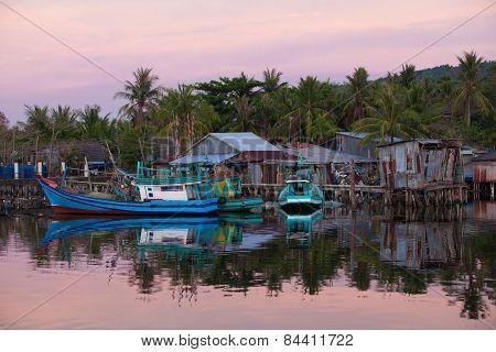 Fishing boats near houses of fishermen