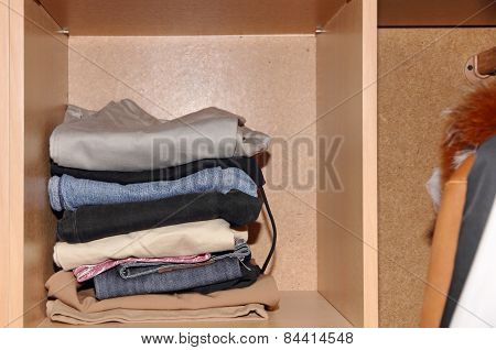 Various Clothes Stack In Wardrobe.