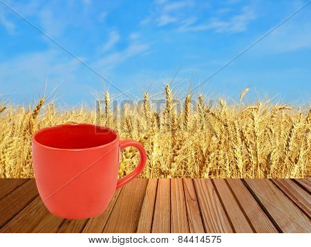 Red Tea Cup On Wooden Surface Against Of Wheat Ears.