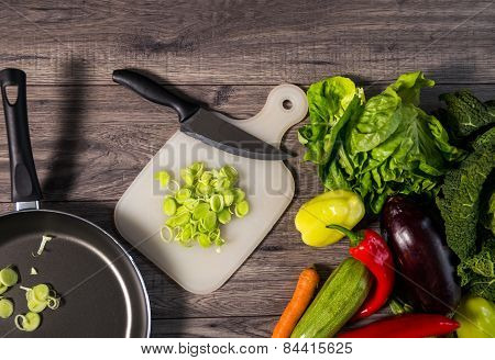 Vegetables On Wooden Background. Stewing leek slices in a frying pan