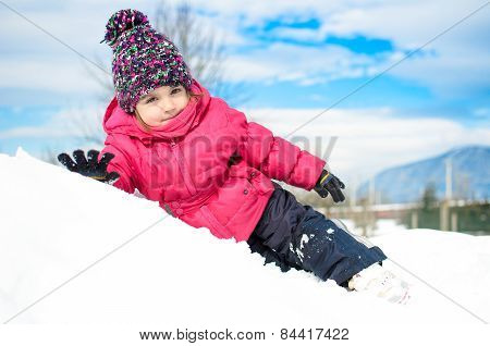 Little Girl In Winter Clothes Laying In Snow Waving And Smiling