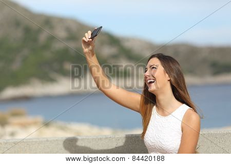 Happy Girl Photographing A Selfie On The Beach