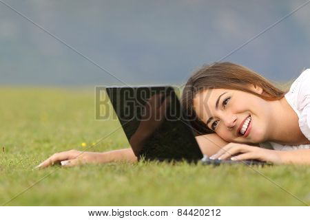 Happy Woman Browsing Internet On A Laptop On The Grass