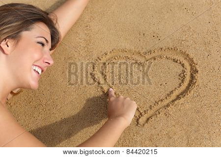 Happy Woman In Love Drawing A Heart On The Sand Of The Beach