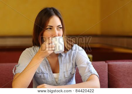 Relaxed Woman Thinking While Is Drinking A Cup Of Coffee